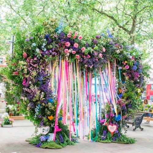 A Bright Colorful Ribbon And Flowers Arch #heartshapedweddingarch #ribbonweddingarch #modernweddingarch