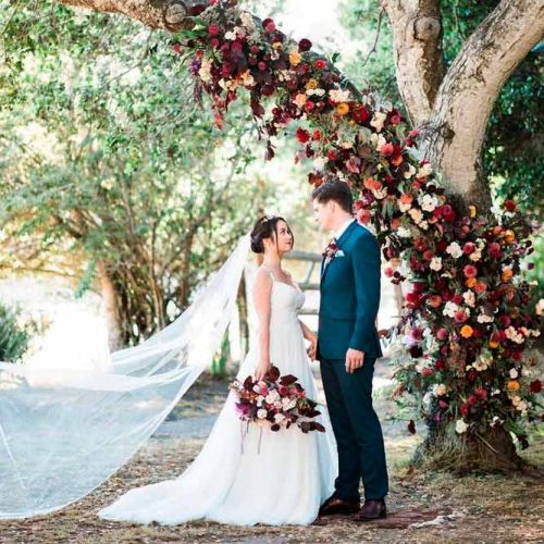 A Ceremony Arch Out Of The Tree Branch With Floral Decorating #outdoorweddingarch #flowersweddingarch